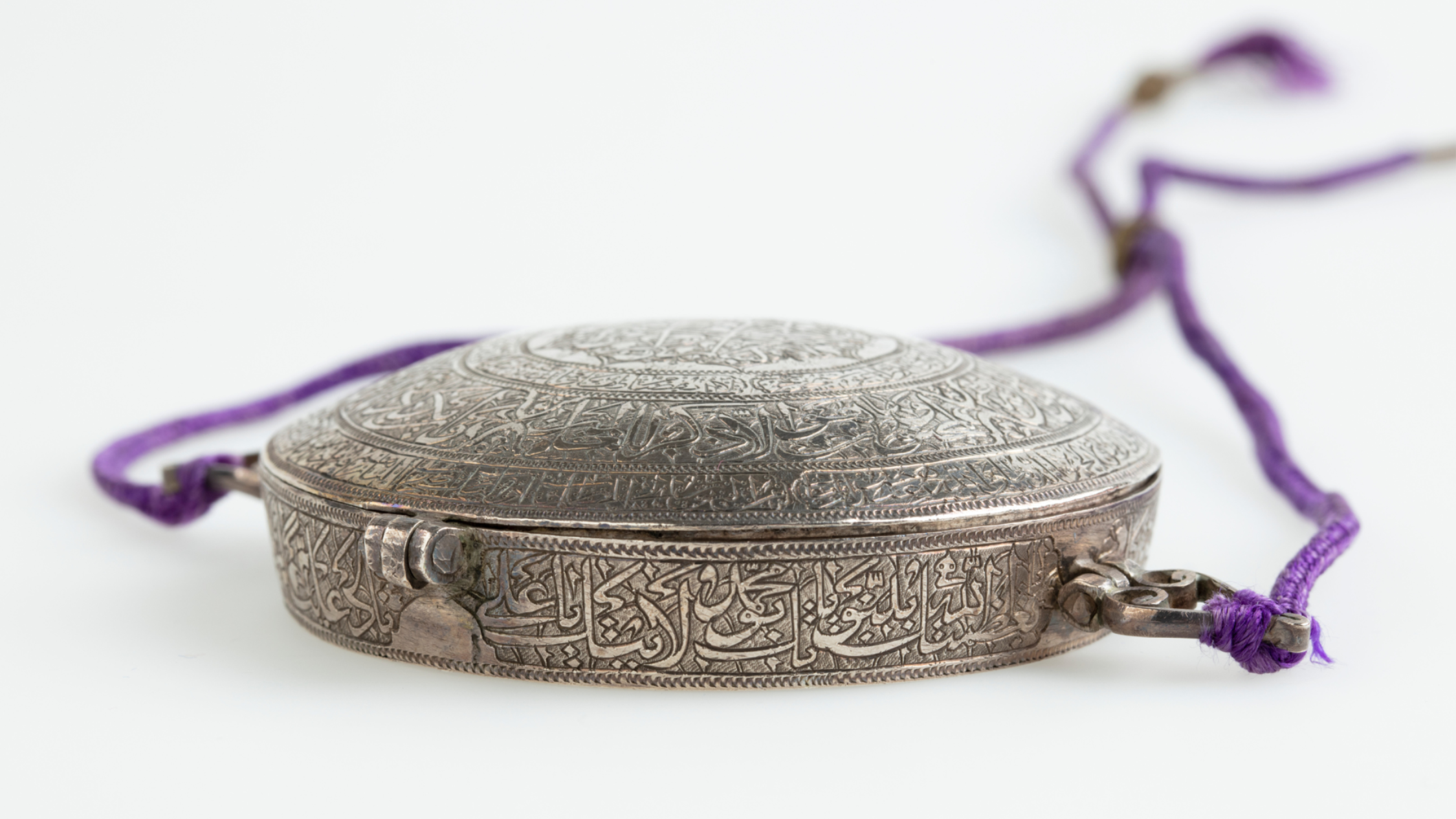 A silver, engraved war amulet on purple thread from 1800s Persia