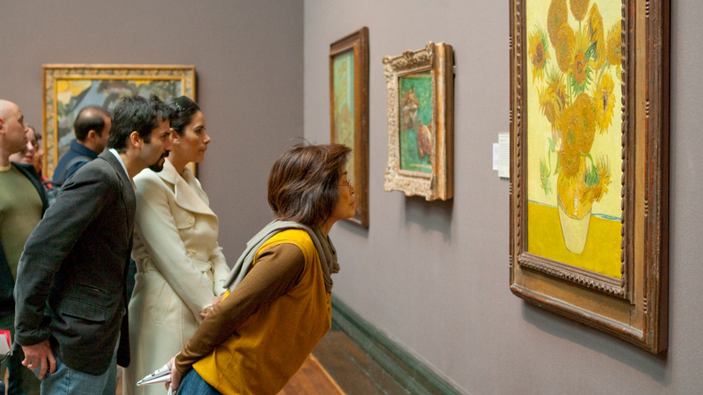 Gallery viewers looking closely at Vincent Van Gogh's 'Sunflowers'