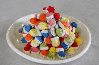 Ceramic fairy iced biscuits in multiple bright colours on a plate