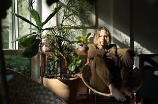 Retrato de una mujer con luz natural y sentada en una silla de mimbre