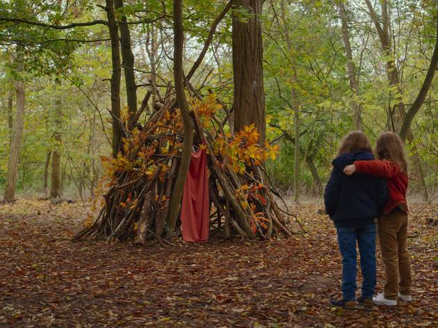 Two young girls hold one another in a woodland setting with a tent mad of branches in front of them