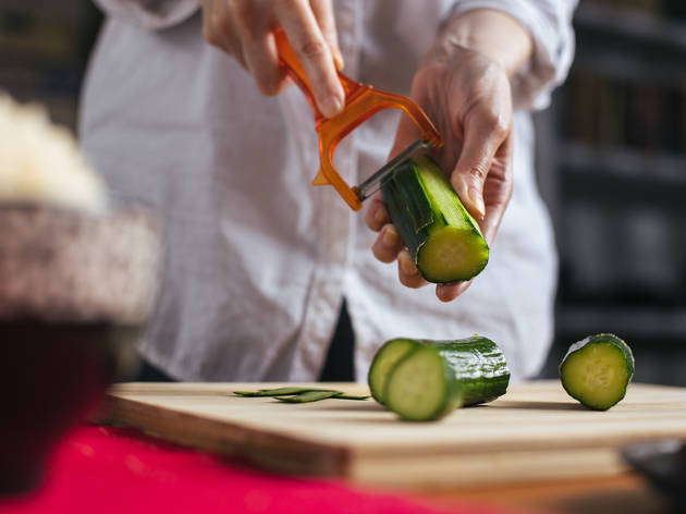 Female chef peeling cucumber in a home kitchen