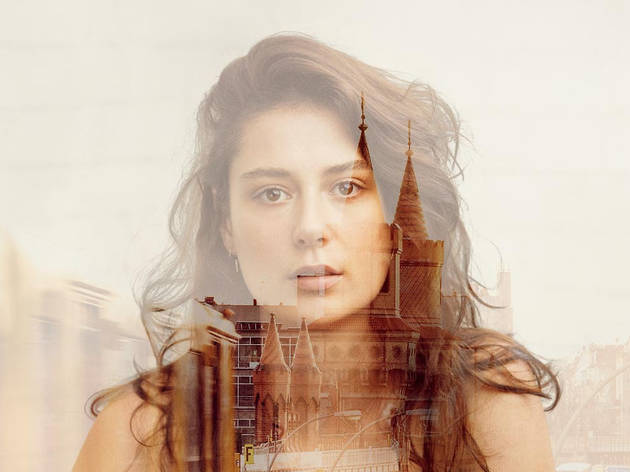 A woman superimposed over a cathedral-like building