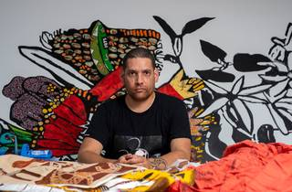 Tony Albert pictured in his studio in front of fabrics and his art on the wall behind him