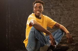 Oliver Twist sits cross-legged, wearing jeans and a yellow tee
