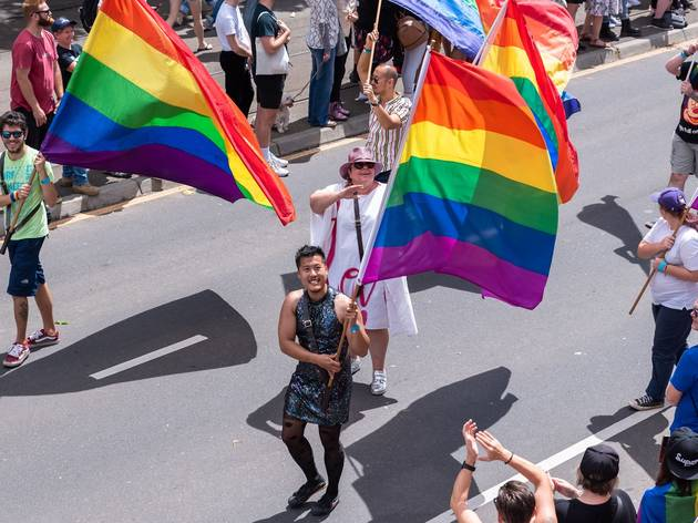 Marches smiling and waving rainbow / LGBTQIA pride flags
