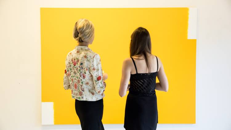 Two women (shot from behind) look at a yellow  painting