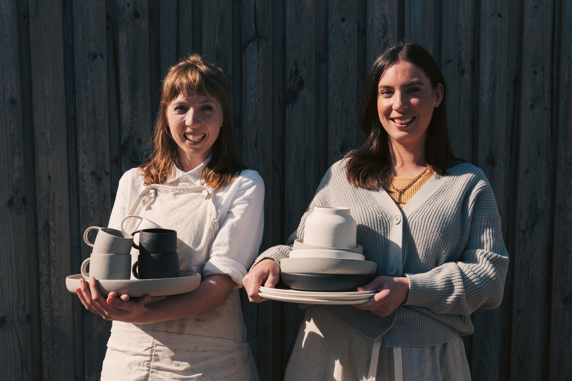 Two people smile holding bundles of grey, black and white ceramics