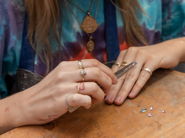 Close up view of a person's hands as they hold a gemstone in tweezers. They are wearing lots of rings and two gold necklaces and have tattoos on their hands and fingers.