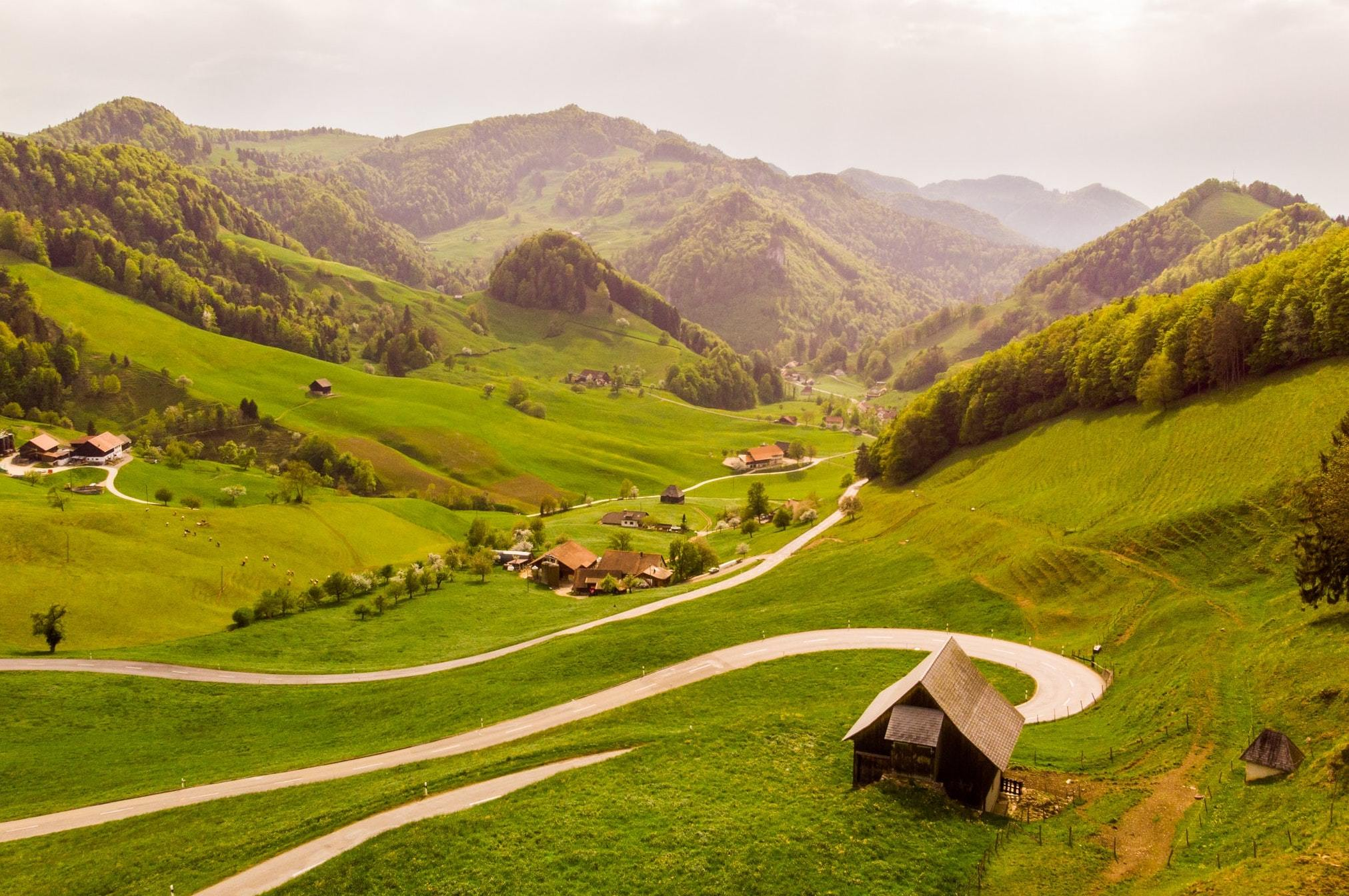 Rolling green hills and a small village in Passwang Pass, Mümliswil-Ramiswil, Switzerland.