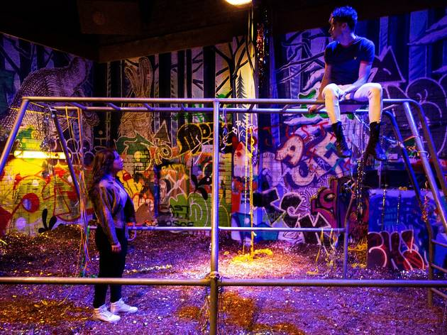 A man sits on a jungle gym in an industrial, heavily grafittied space. He looks down at a woman who is peering up at him.