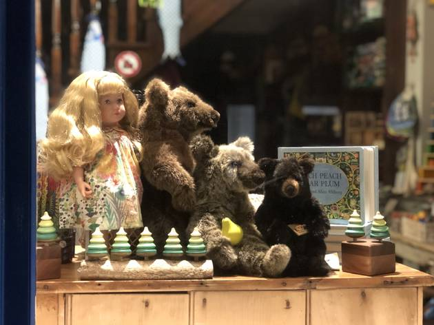 A blonde doll, three stuffed bears and a selection of books and wooden toys in the window of Puddleduck Toys