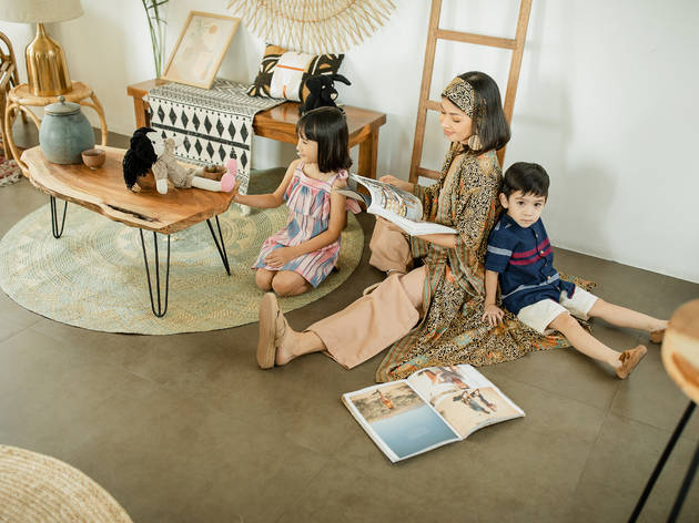An adult and two small children sit on the floor surrounded by toys, furniture, rugs and bric-a-brac from Frankie General Store