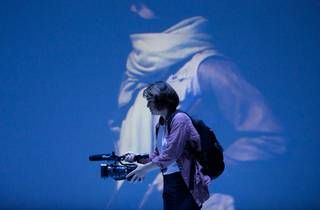 Sheridan Harbridge, as war reporter suzie, carries a hand held camera, with a projection of a scarf-wearing woman behind her