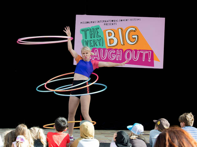 A performer entertains a crowd of kids with an impressive amount of hula hoops