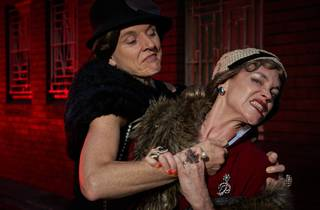 Two women in 1920s clothing fight each other
