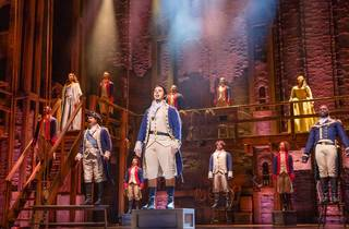 The cast of Hamilton in frock coats, standing on boxes on stage