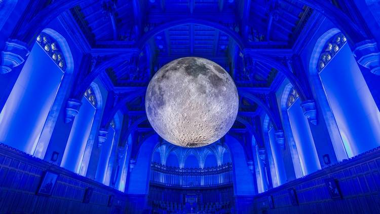 A illuminated moon sculpture in a blue lit room