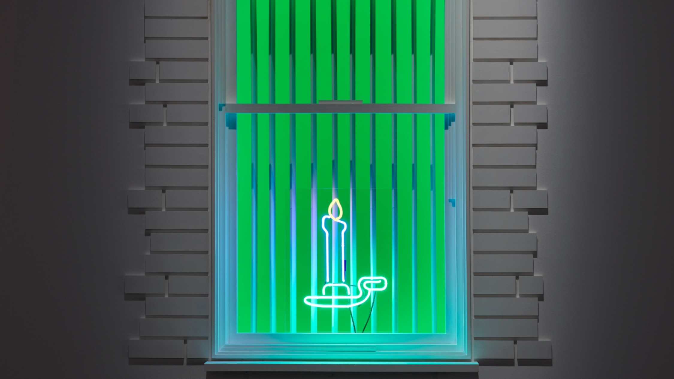 A neon blue candle on green backdrop, set n white brick wall