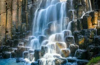Caída de cascada sobre rocas en forma de prismas