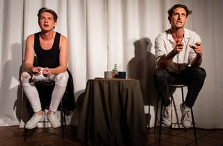 Two men sit on stools either side of a small table