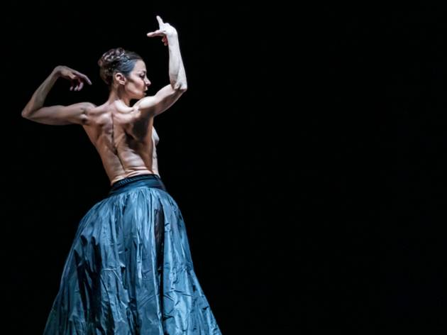 A woman in a ruffled silk blue skirt, bare back, holds her arms aloft dramatically
