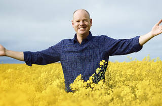 Tom Gleeson, wearing a blue checkered shirt, standing arms outstretched in a fields of bright yellow flowers.