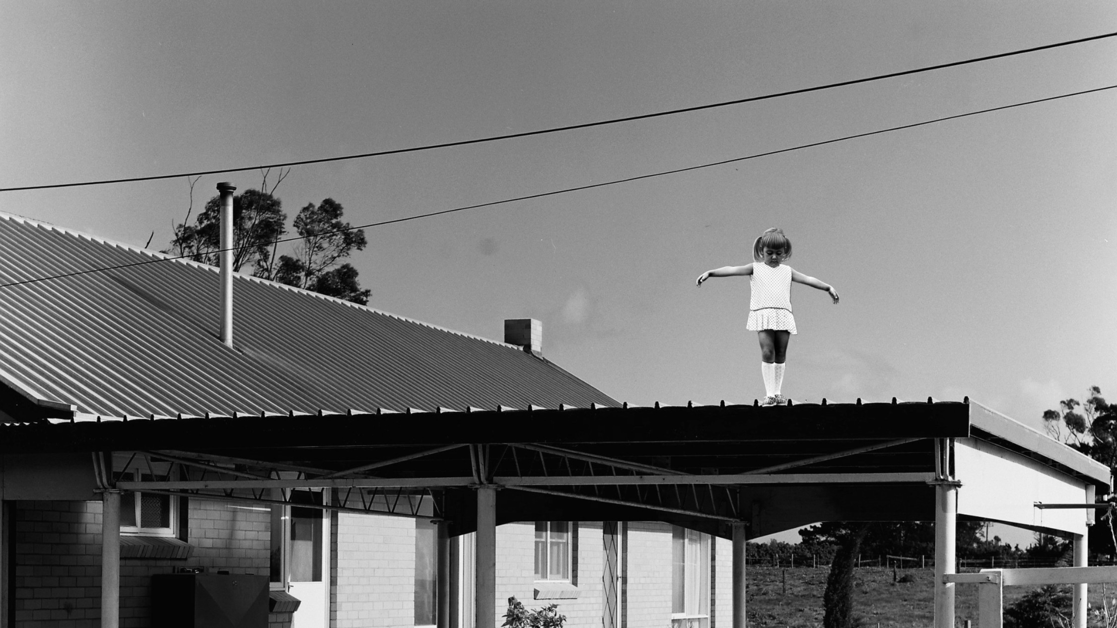 A girl stands on top of a car port