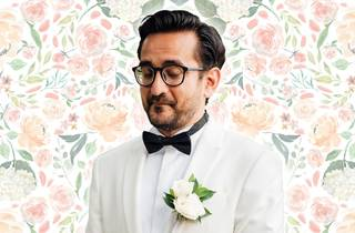 Comedian Sami Shah in white wedding tux in front of pastel floral wallpaper