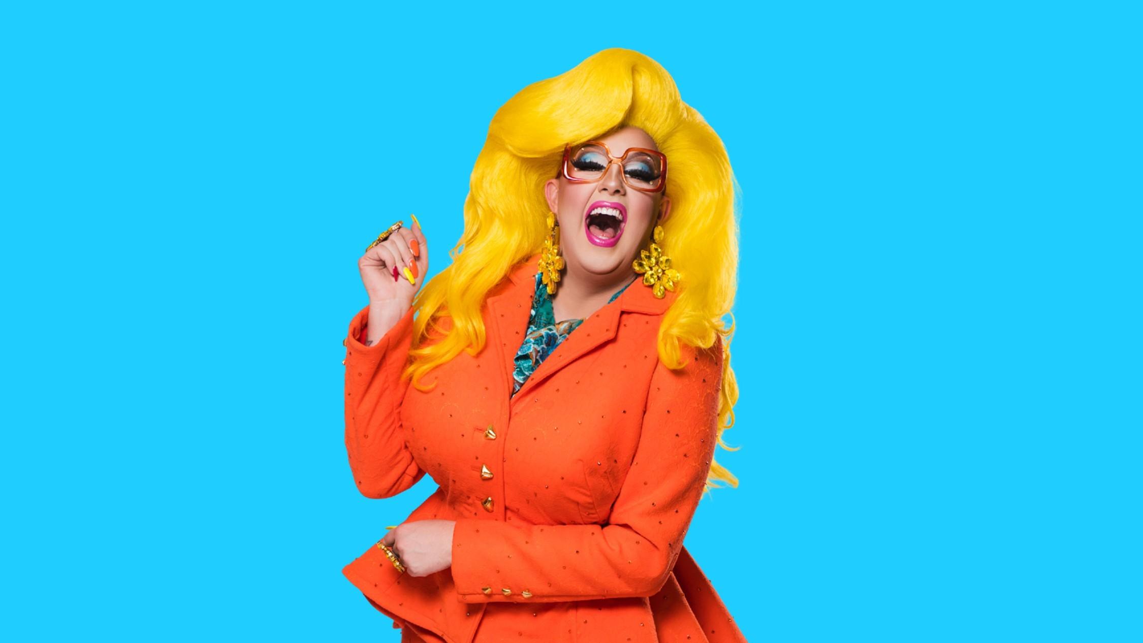 Darg queen Karen From FInance in an orange suit and huge yellow wig