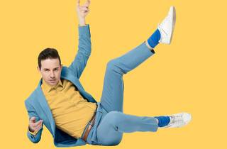 Nath Valvo legs akimbo in a pale blue suit against a yellow backdrop