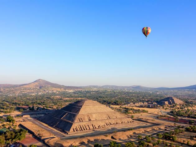 Imagen panorámica de las pirámides de Teotihuacán con globo aerostático de fondo