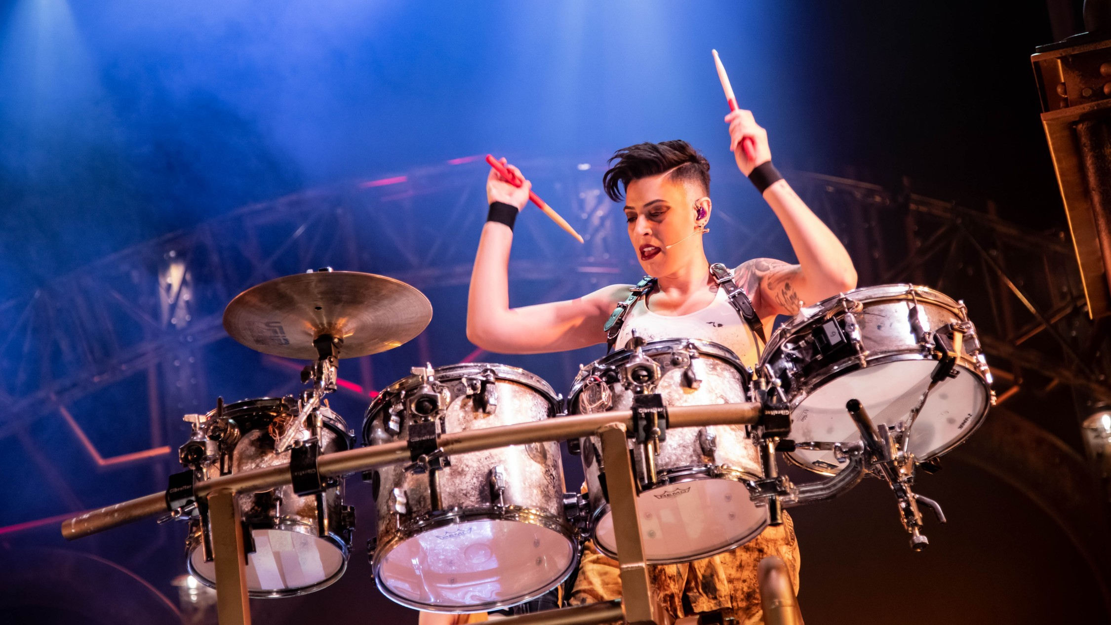 A woman wearing a white singlet, black wrist cuffs and a short spiky hair cut looms over a drum kit, mid performance