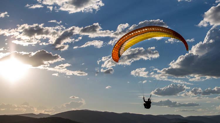 Toma abierta de una persona volando en parapente