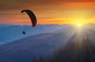 Imagen aérea de una persona volando en parapente durante el atardecer