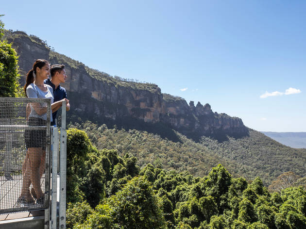 A couple look out over the Jamison Valley from the Katoomba Falls lookout