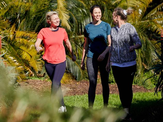 Three women wearing activewear smiling and walking through a grassy path surrounded by palms, ferns and flowers
