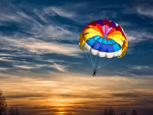 Exterior con una persona cayendo en paracaídas