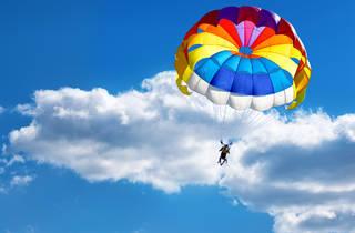 Exterior con toma del cielo y una persona saltando en paracaídas