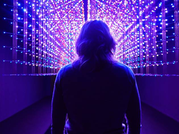 a person stands in front of a suspended wall of LED lighting like a starfield