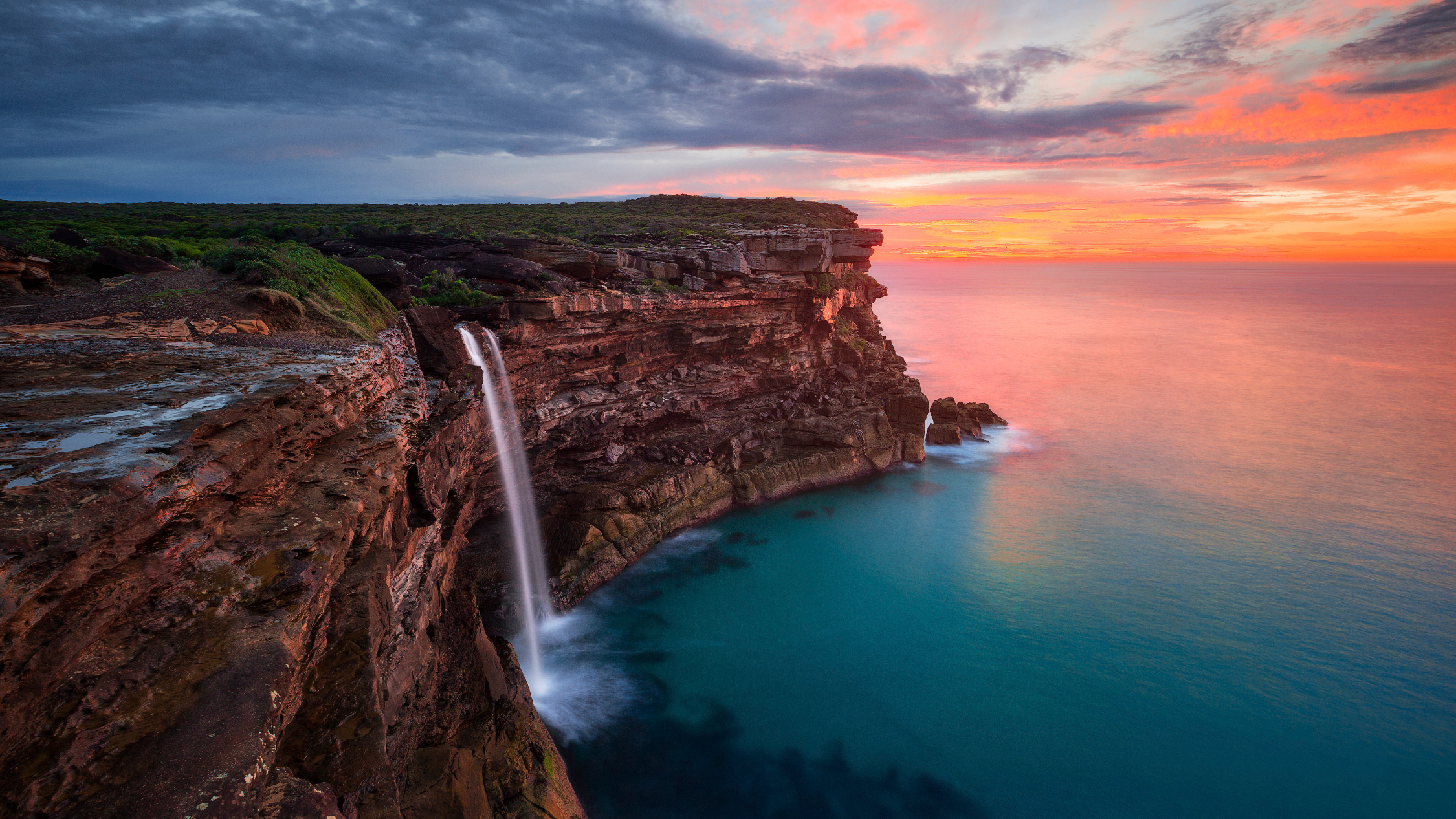 The sun sets over the ocean in the background with Eagle Rock and the Currarrong Falls in the fore.