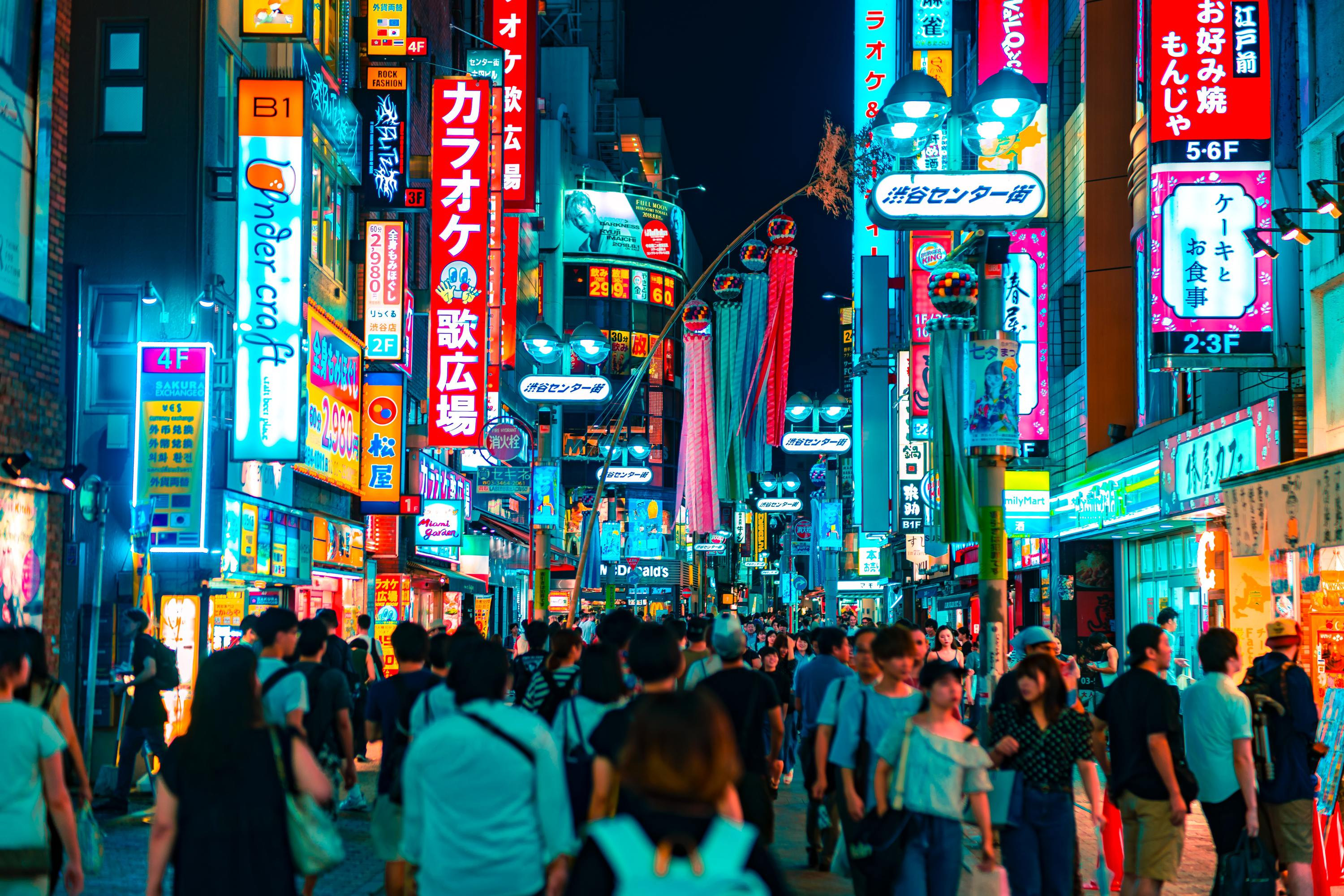 A crowd of people walking on a brightly lit street at night