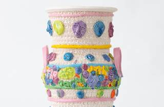 A cute ceramic urb in pastel shades with faces and flowers adorning it