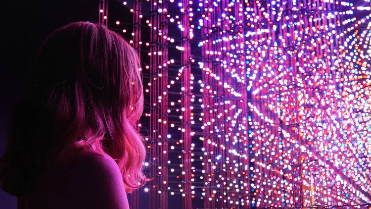 Person with long hair stares at led light artwork