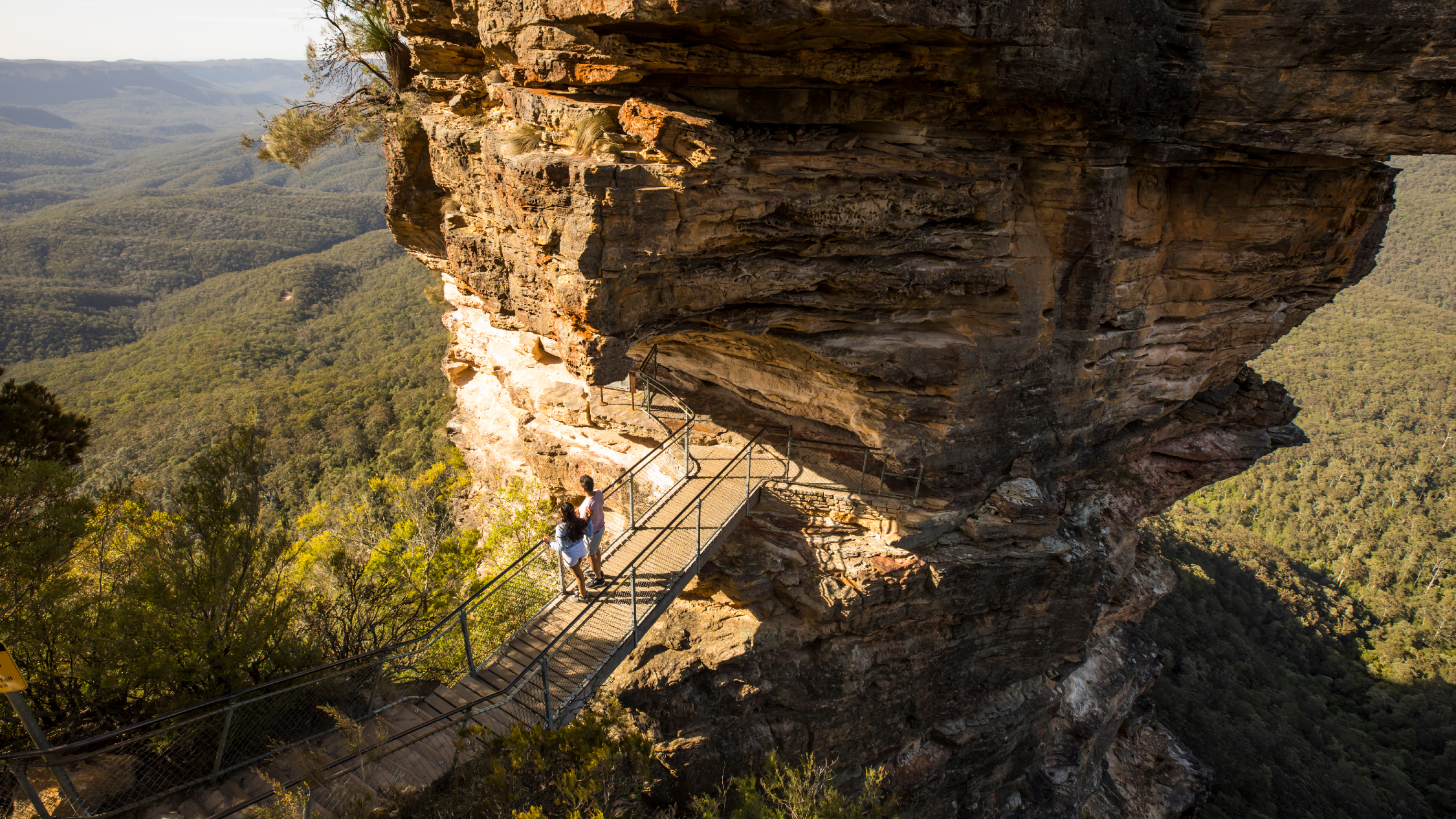 Two people stand on Honeymoon Bridge, looking out over the Jamison Valley next to the Three Sisters.