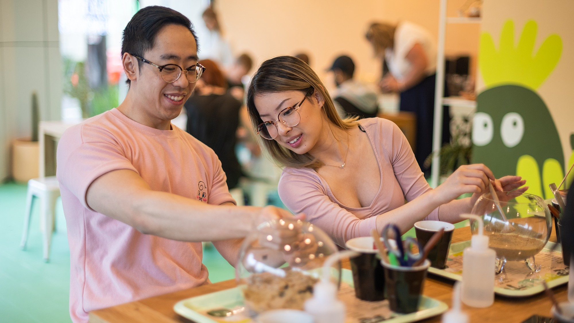 Two people sit at table, they are building terrariums.