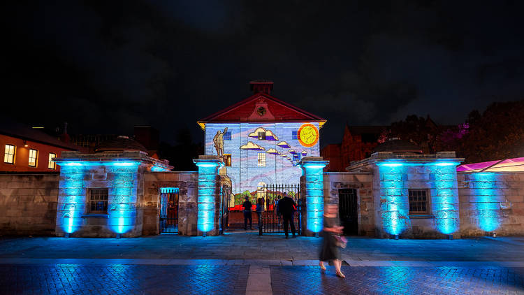 The Hyde Park Barracks at night, the sandstone illuminated in bright blue, with an artwork projected onto the main buildling.