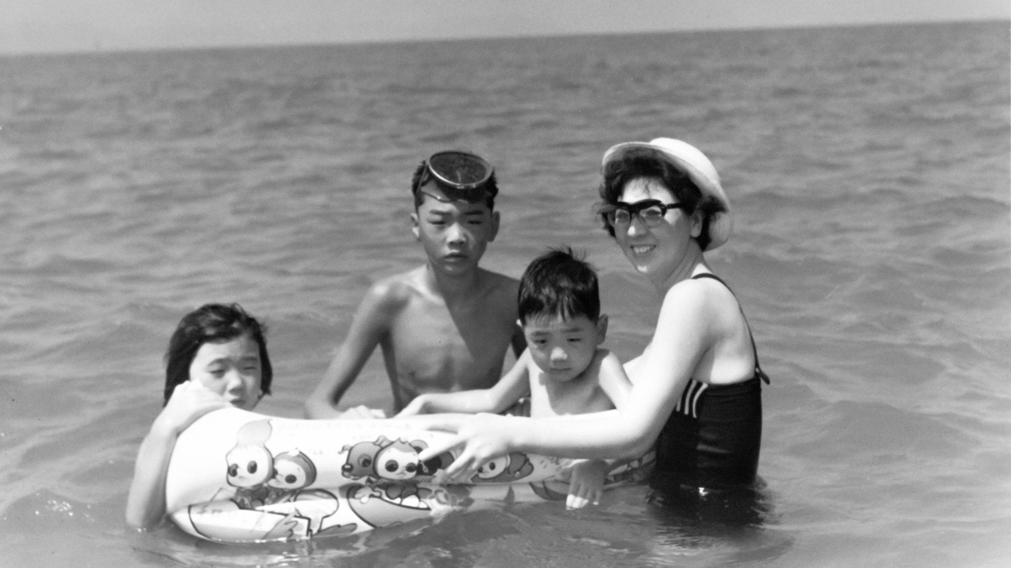 In a black and white photo a woman and three children are at the beach, they are in the water with a floatie device