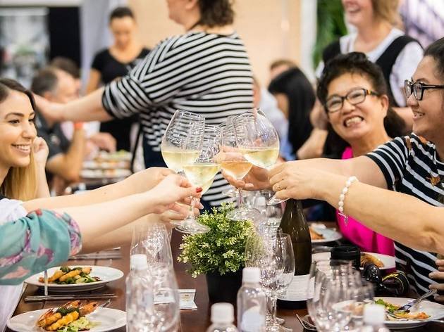 Six people clinking wine glasses across a table