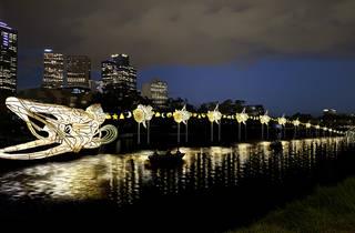 A glowing eel sculpture alongside the Yarra River